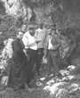 Recto: Spanien 1909: Vor dem Eingang der Höhle von Castillo. Im Nachdruck des El Hombre Fósil von 1985, S. 07 findet sich dazu folgende Angabe: 23. Juli 1909: S. A. Albert I. von Monaco (rechts sitzend) lauscht den Erklärungen des Abbé Henri Breuil (in Soutane links) und des Anthropologen Marcelin Boule (mit Kappe); dazwischen Hugo Obermaier und rechts mit dem Hut in der Hand Hermilio Alcalde del Río. Verbleib: Archiv der Hugo Obermaier-Gesellschaft, Erlangen.