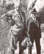 Recto: Hugo Obermaier am 26. März 1940 vor der spätpaläolithischen Fundstelle am Wachtfelsen bei Grellingen (Schweiz). Beschriftung: Das Foto ist auf eine kleine Karte aufgeklebt mit der Beschriftung: Gansser – Obermaier – Tschumi. Am Wachtfelsen (Azilien bei Grellingen. 26. März 1940). Foto: R. Laur-Belart, Basel. Verbleib: Archiv der Hugo Obermaier-Gesellschaft, Erlangen.